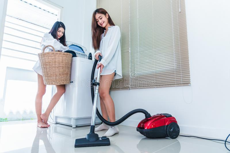 Two Asian women doing housework and chores in kitchen. Indoors activity and Lifestyles concept. Beauty lesbian theme royalty free stock photo