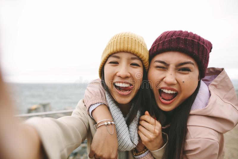 Two asian women friends having fun standing outdoors royalty free stock photography
