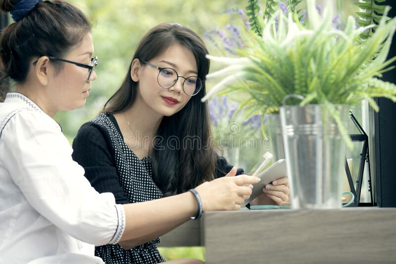 Two asian woman with smart phone in hand talking  in home living room with happiness face stock photography