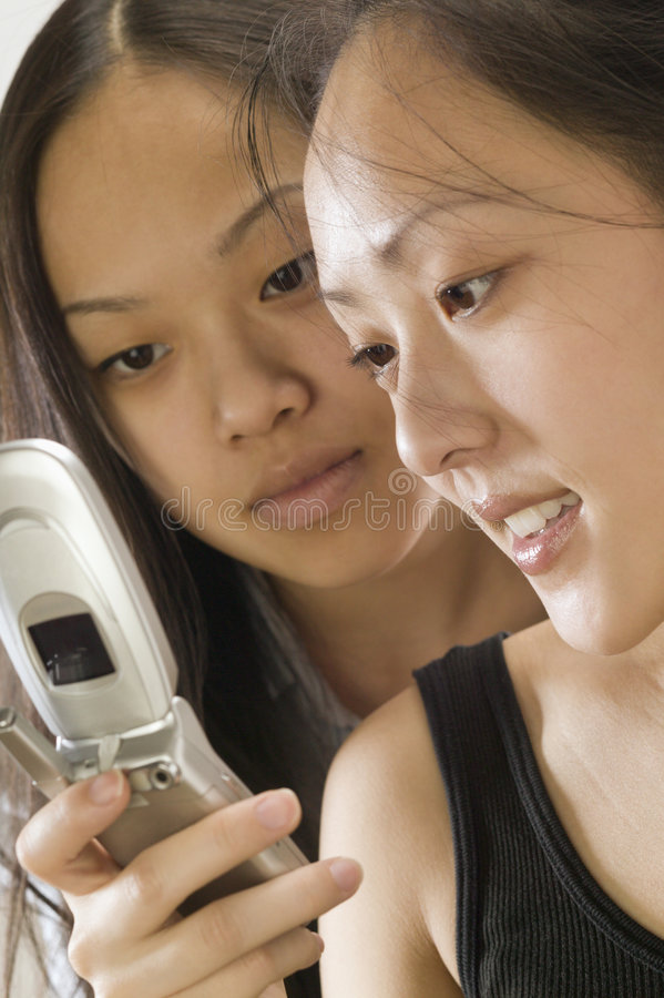 Two Asian women using cell phone royalty free stock photography