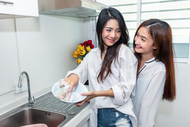 Two Asian women washing dishes together in kitchen. People and L royalty free stock photos