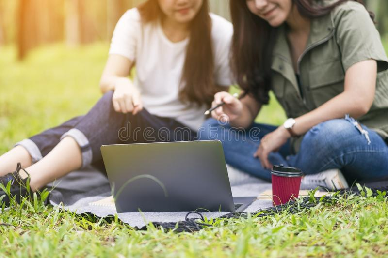 Two asian women working and using laptop computer in the park stock photo