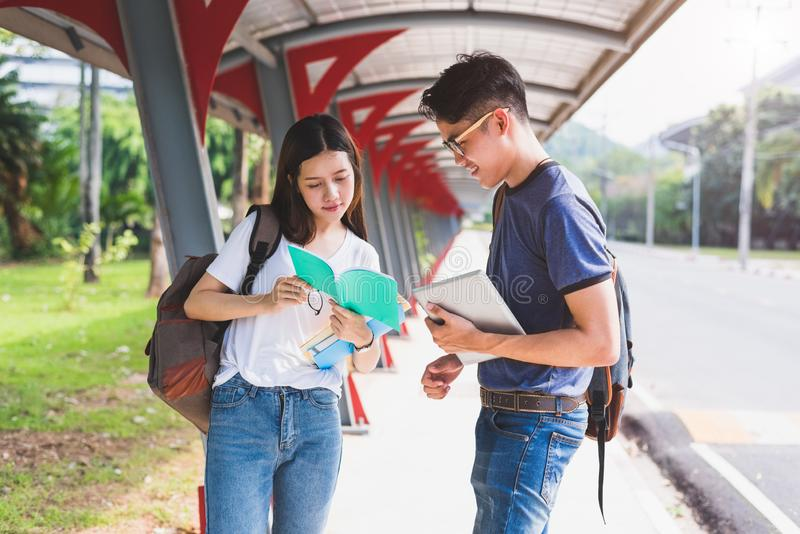 Two Asian young college people discussing about reading book and stock photo