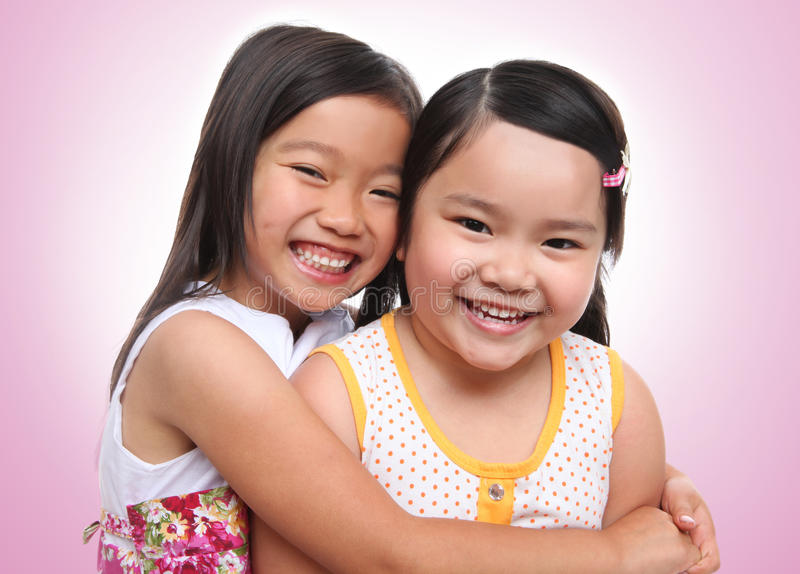 Two asian young sisters hugging stock image
