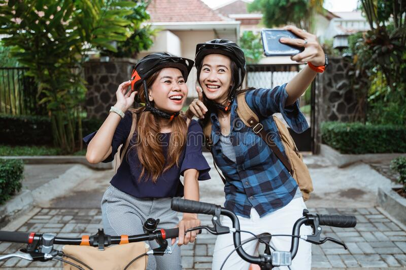 Two asian young woman wearing helmet and bags with camera cellphone make a video content on folding bike stock photos