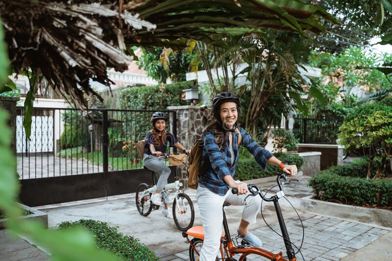 Two asian young woman wearing helmet and bags ready go to campus royalty free stock photo
