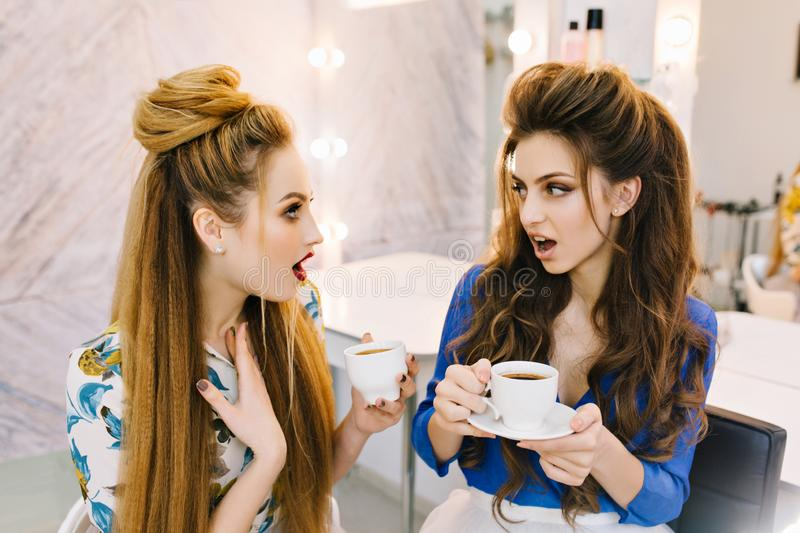 Two astonished surprised attractive women talking in beauty salon. Drinking coffee, preparing to party, having fun stock photography