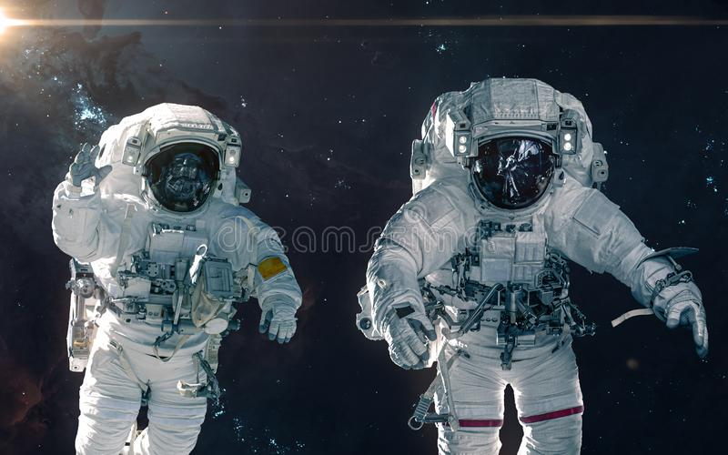 Two astronauts on background of nebulae and star clusters. Deep space landscape. Science fiction. Elements of this image furnished by NASA royalty free stock photos