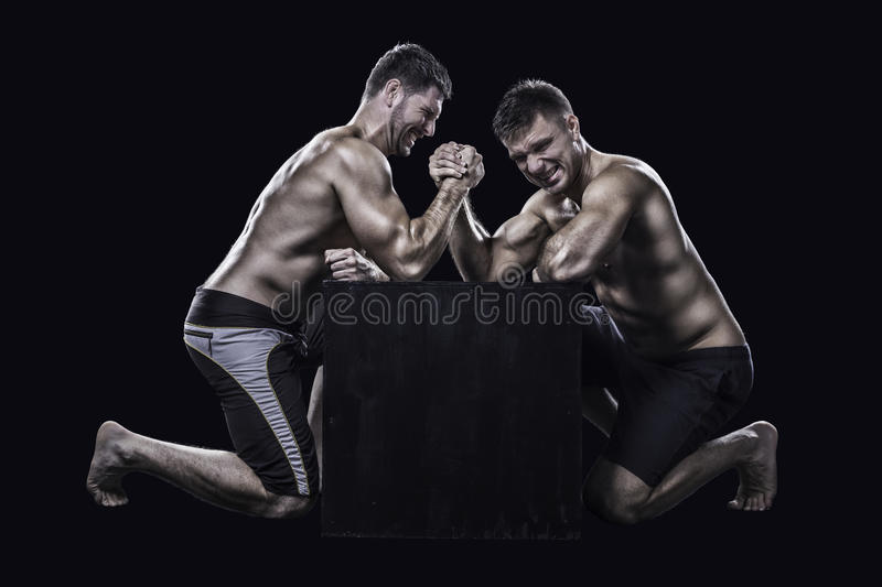 Two athletes arm wrestling. Two muscled young athletes have a hard arm wrestling match on a black box shirtless royalty free stock photo