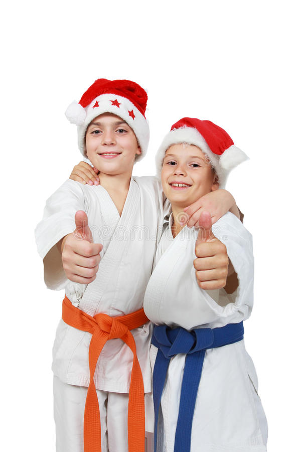 Two athletes in the cap Santa Claus show finger super. Athletes in the cap Santa Claus show finger super stock images