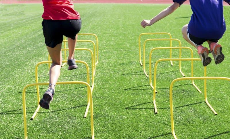 Two athletes jumping over yellow mini hurdles stock photos