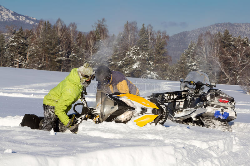 Two athletes pull a snowmobile. royalty free stock photo