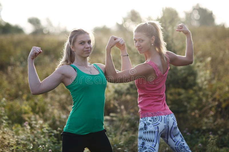 Two athletic girls flexing their arm muscles stock photo