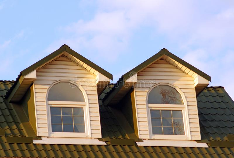 Two attic windows with white frames on the roof of red tiles royalty free stock image