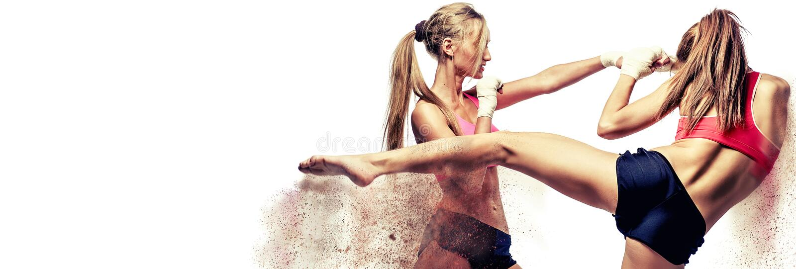 Two attractive athletic girls fighting, standing on defence pose image with digital effects sandy fragments. stock photos