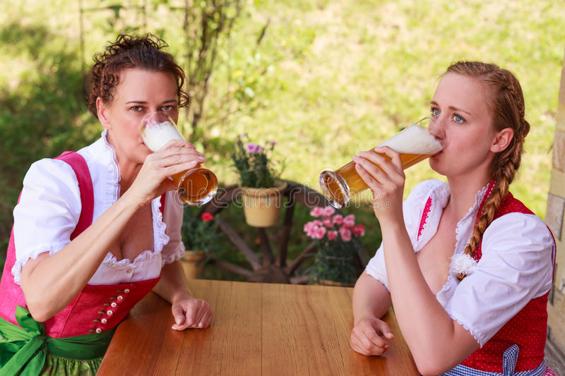 Two attractive Bavarian women drinking beer stock photos