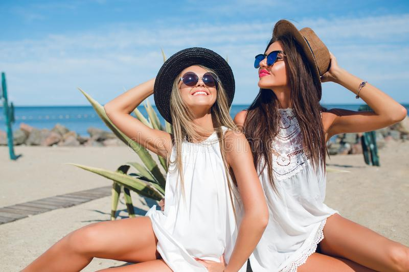 Two attractive brunette and blonde girls with long hair are sitting on the beach near sea. They wear hats, sunglasses. And white dresses. They are posing and royalty free stock image