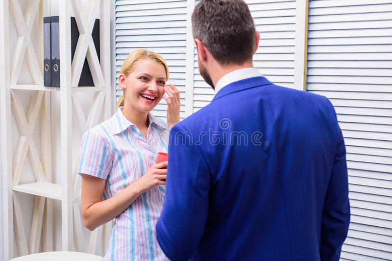 Two of attractive business people, standing next to each other, holding a cups, smiling standing at office. Smiling royalty free stock photo
