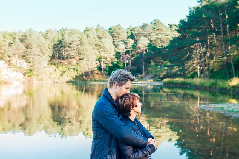 Two attractive dreamy people, couple in casual outfit at wild forest near water. Idyllic calm peaceful life style person freedom stock photos