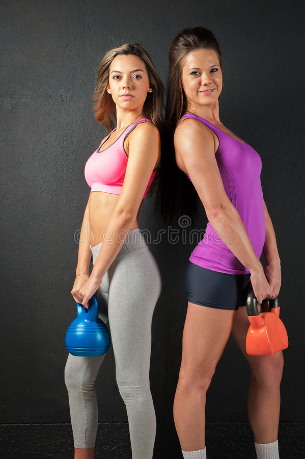 Two Attractive female fitness models isolated on a black background. Two Attractive female fitness model isolated on a black background in sports wear with royalty free stock photo