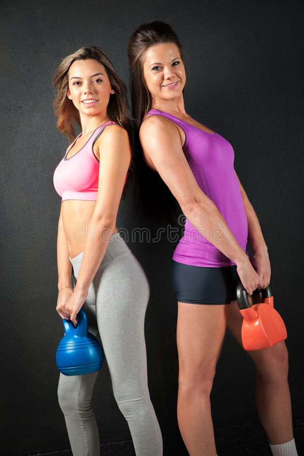 Two Attractive female fitness models isolated on a black background background. Two Attractive female fitness model isolated on a black background in sports wear stock images