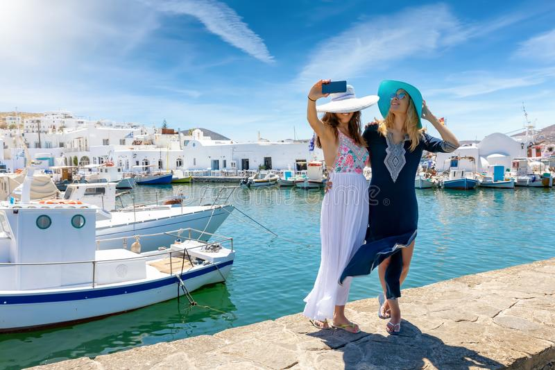 Two female friends taking selfie photos at the fishing village Naousa royalty free stock image