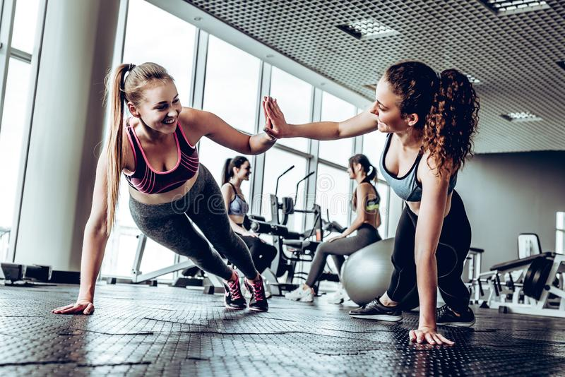 Two attractive fitness girls doing push ups. Girls give five each other. Gym background royalty free stock photography