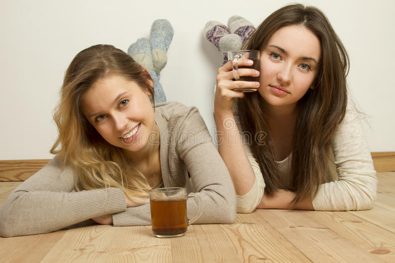Two attractive friends drinking tea stock images