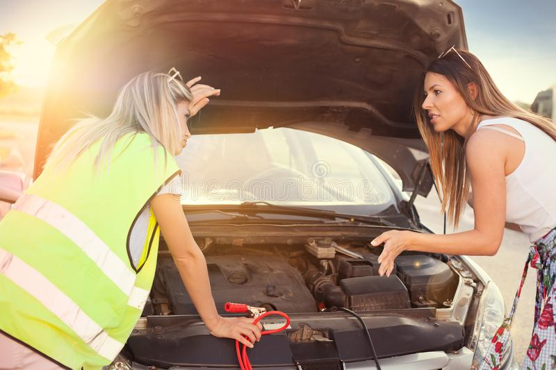 Two attractive girl in safety yellow vest fixing car stock photos