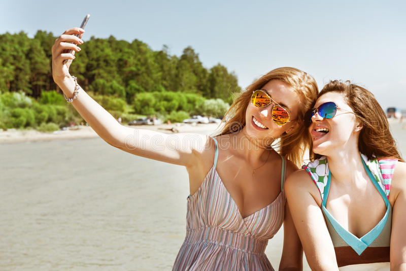 Two attractive girl standing together, posing and doing selfie beach royalty free stock image