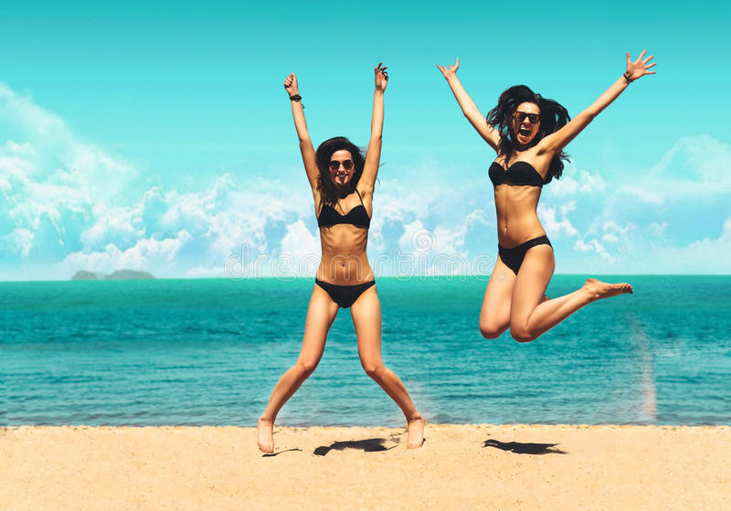 Two Attractive Girls in Bikinis Jumping on the Beach. Best Friends Having Fun, Summer vacation holiday Lifestyle. Happy stock photography