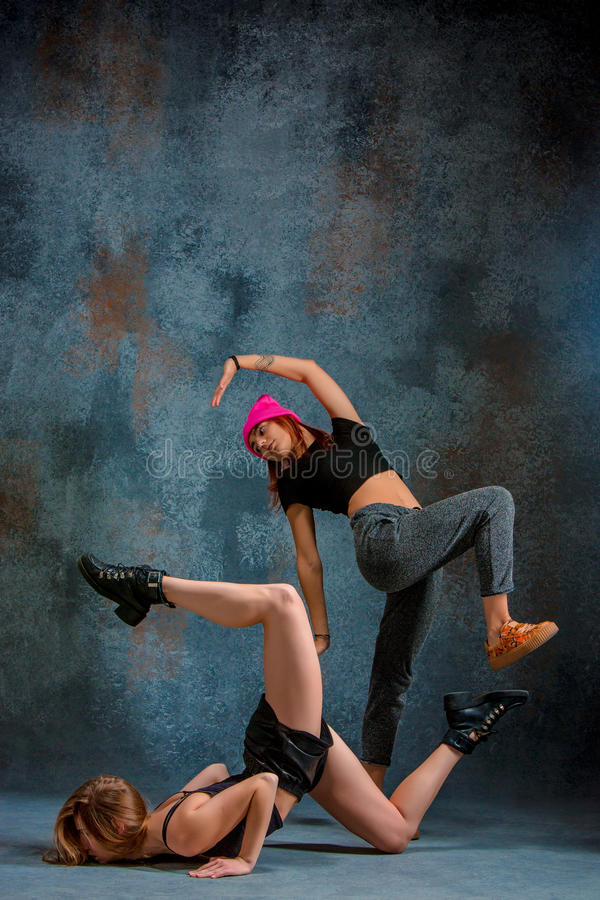 The two attractive girls dancing twerk in the studio. The two attractive girls dancing twerk iat the blue studio background stock photography