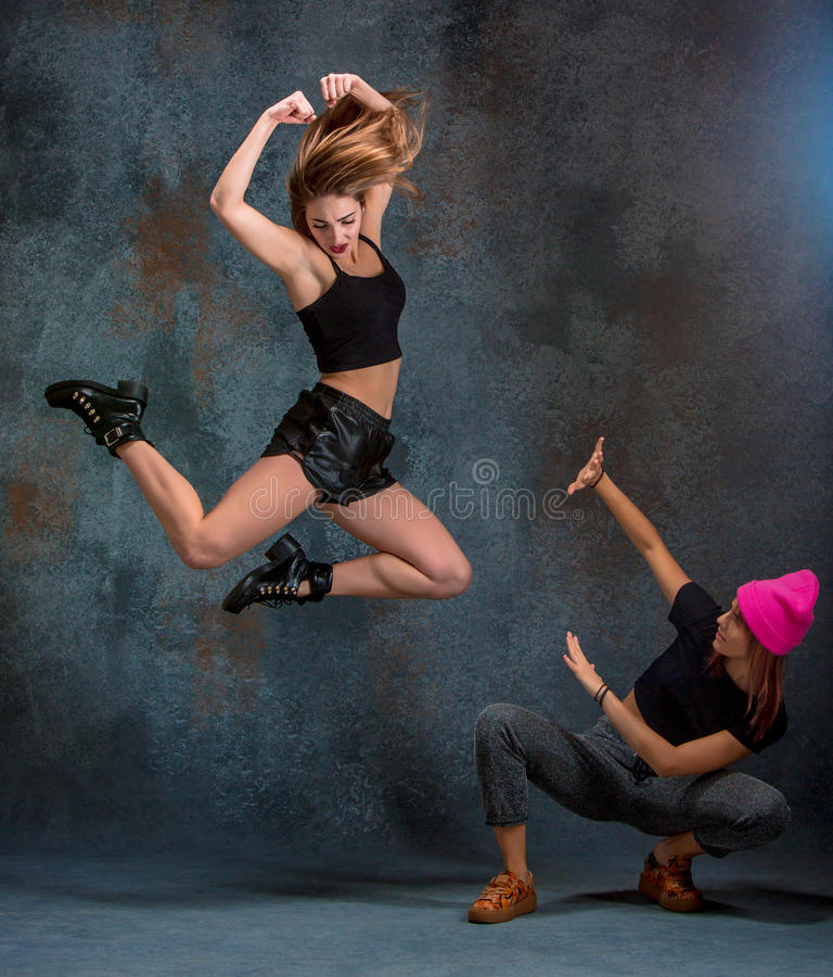 The two attractive girls dancing twerk in the studio. The two attractive girls dancing twerk iat the blue studio background royalty free stock photo