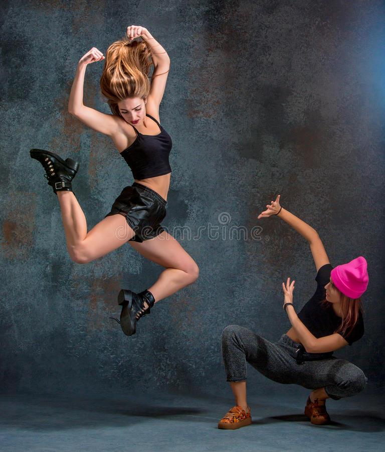 The two attractive girls dancing twerk in the studio. The two attractive girls dancing twerk iat the blue studio background stock photo