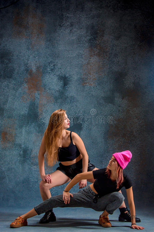 The two attractive girls dancing twerk in the studio. The two attractive girls dancing twerk iat the blue studio background stock image