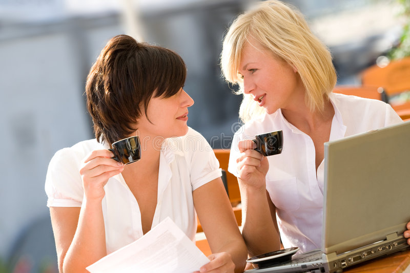 Two attractive girls with laptop drinking coffee stock photos