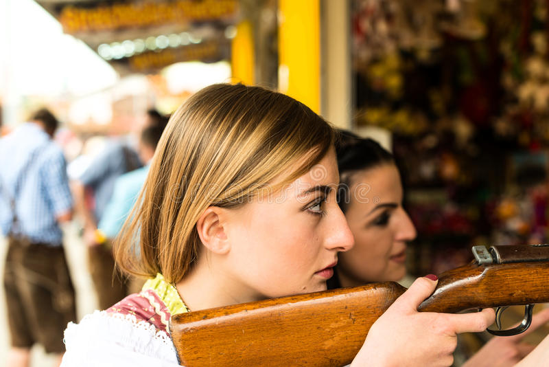 Two attractive girls playing shooting games at. German funfair Oktoberfest, wearing traditional Dirndl dresses stock photography