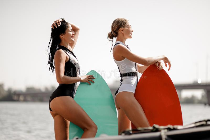 Two attractive girls standing with wakeboards on the lake. Two attractive girls in the black and white and red swimsuit standing with the wakeboards royalty free stock images