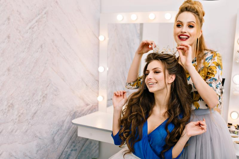 Two attractive joyful models with stylish look having fun in beauty salon. Preparing to party, carnival celebration royalty free stock photography