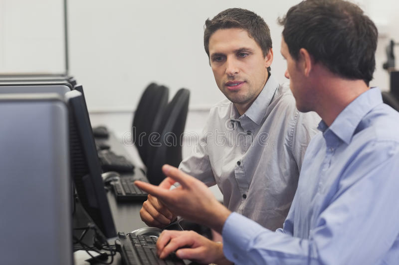 Two attractive men talking in computer class royalty free stock image