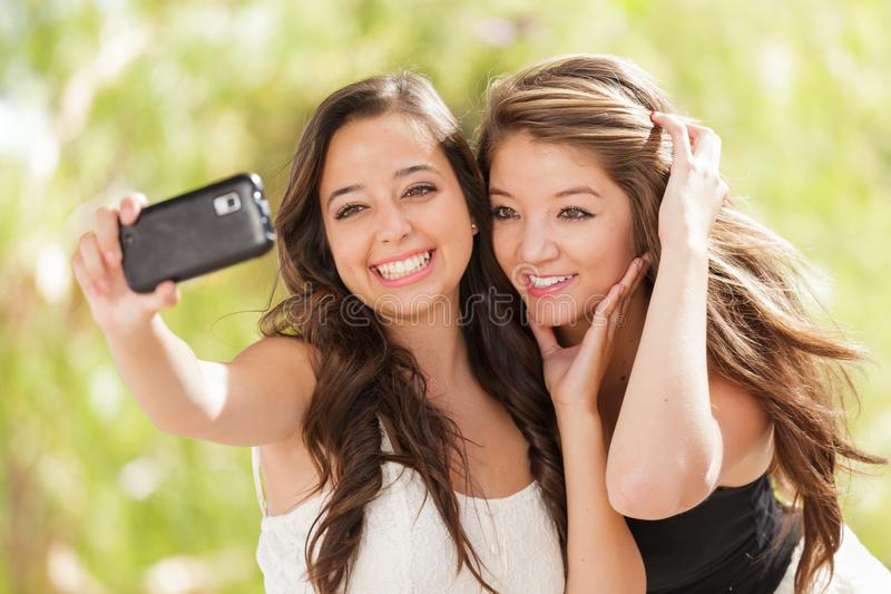 Two Attractive Mixed Race Girlfriend Teens Using a Smartphone. Two Attractive Mixed Race Girlfriends Using Their Smart Cell Phones For Selfie Outdoors royalty free stock image