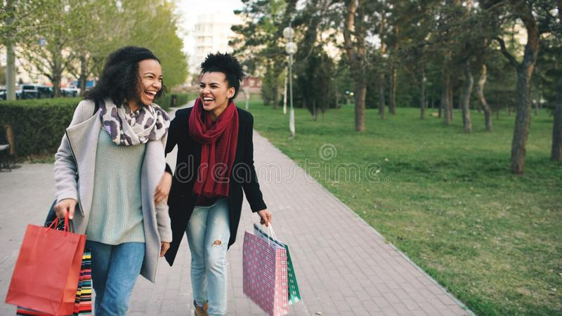 Two attractive mixed race women dancing and have fun while walking down the park with shopping bags. Happy young friends royalty free stock photography