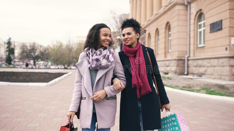 Two attractive mixed race women with shopping bags talking and walking down the street. Girlfriends have fun after stock photos