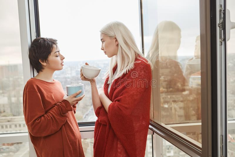 Two attractive and sensual girlfriends standing near opened window in red clothes while drinking coffee royalty free stock photo
