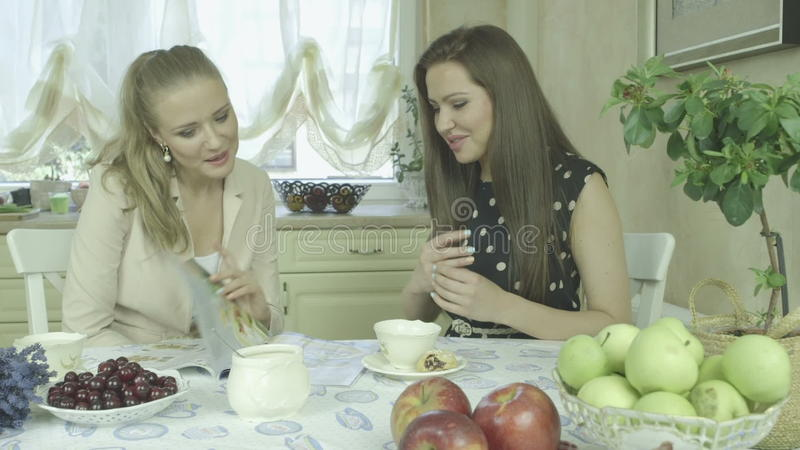 Two Attractive Smiling Young Friends Having Relaxing Time At Dining Table  Stock Footage - Video of kitchen 673138edc