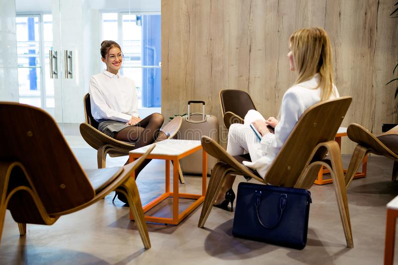 Two attractive stylish businesswomen talking about working at the hotel lobby stock photos