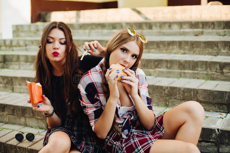 Stylish students girls having breakfast and eating fast food. stock photography