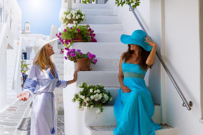 Two attractive traveler woman are enjoying the white, picturesque alleys of Mykonos. Two attractive traveler women are enjoying the white, picturesque alleys of stock photo