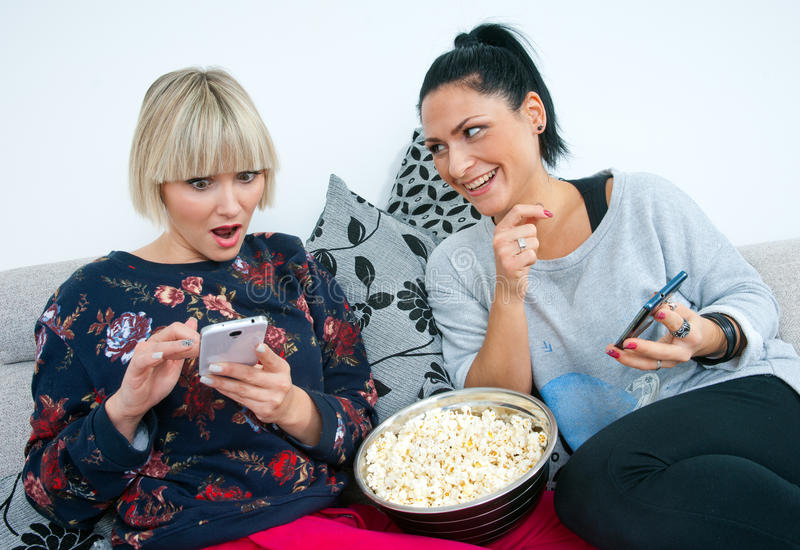 Two attractive woman friends with mobile phone and popcorn royalty free stock photography