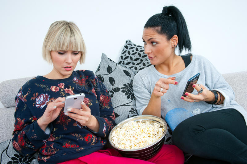 Two attractive woman friends with mobile phone and popcorn royalty free stock images